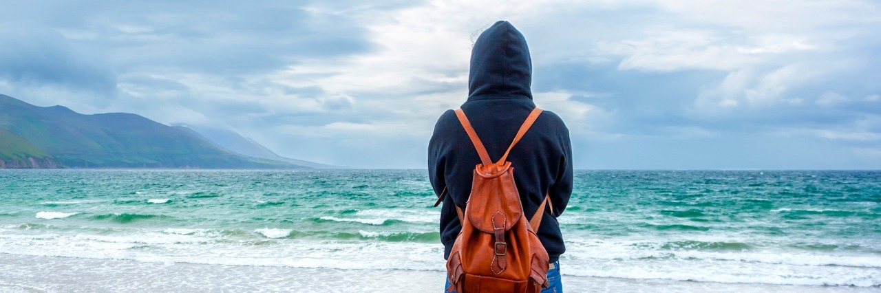Person wearing hoodie and backpack, standing in front of ocean on cloudy day