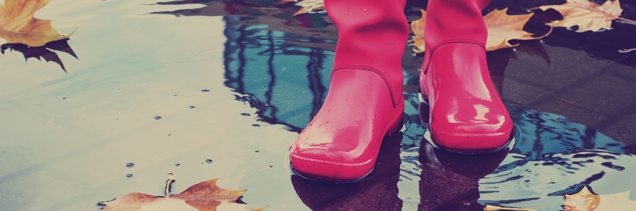 woman wearing pink rain boots standing in autumn puddle with leaves