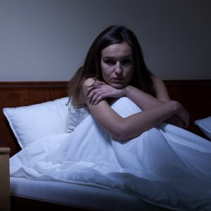 young woman with insomnia or after nightmare sitting up in bed