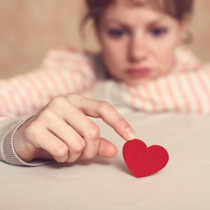 sad girl holding heart by tip of finger on table
