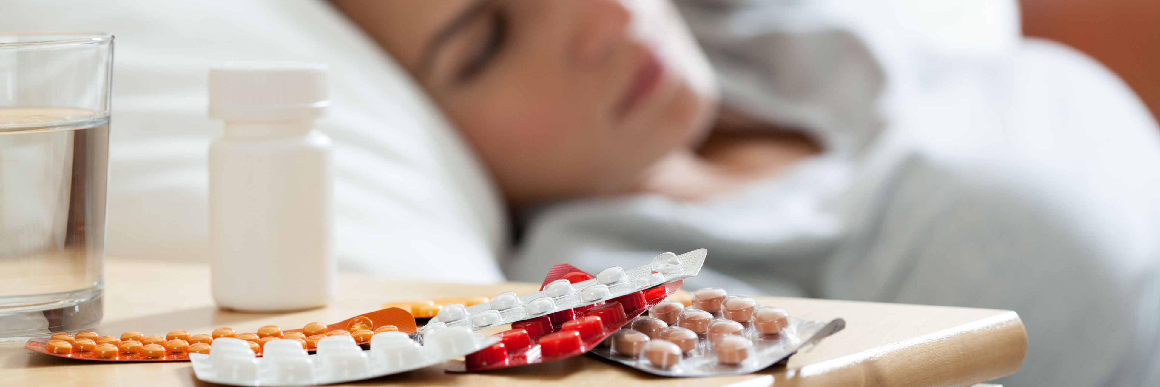 medication on night table in bedroom beside unwell looking woman