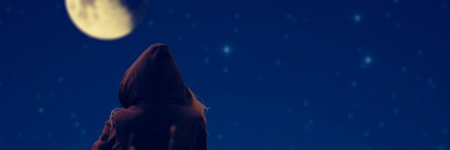 girl in a hoodie sitting outside at night and looking at the moon