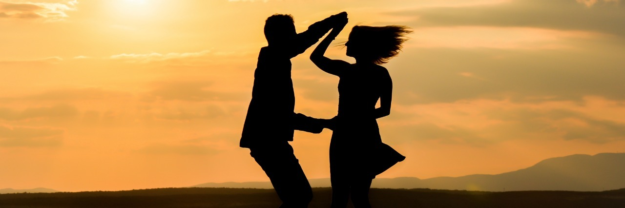 silhouette of man and woman dancing together by the ocean at sunset