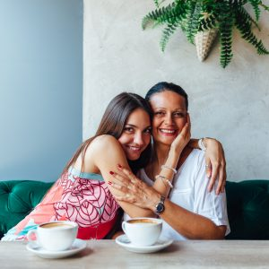 Love of mother and daughter. Aged woman and her adult daughter drinking coffee at cafe. Mothers day.