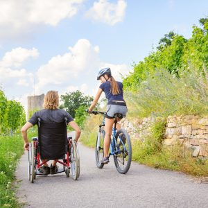 Friends enjoying the outdoors, one using a wheelchair and the other riding a bicycle.