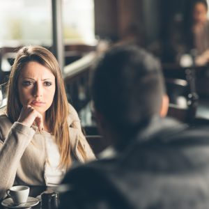 man and woman on a date at a bar, and the woman is frowning