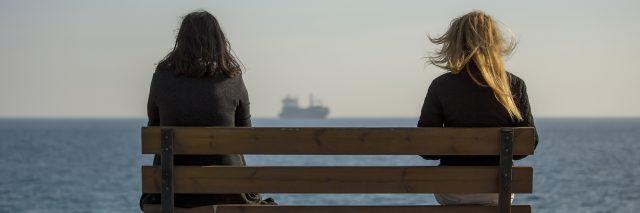 two women sit bench near beach