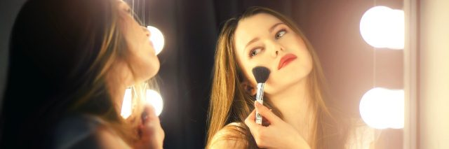 Young woman looking into mirror, putting on blush.