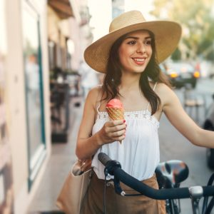 A woman walking with her bike holding an ice cream cone