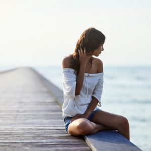 A young woman sits on a pier, staring into a body of water.