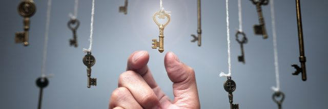 Keys are dangling from ceiling as a hand reaches up to pick one.