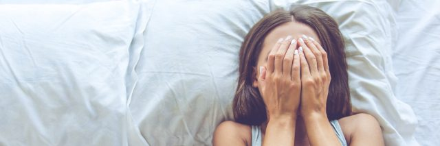 woman covering her face in bed
