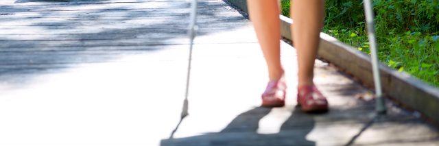 woman walking down a sidewalk with walking sticks