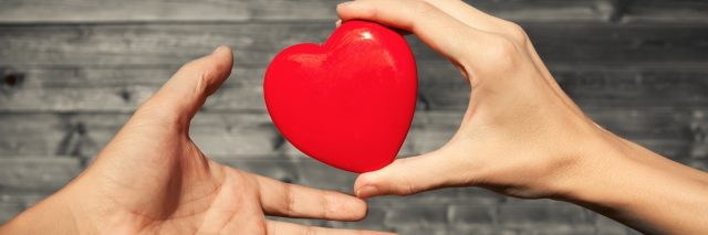 two hands exchanging a red heart
