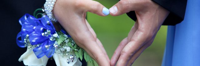 A couple going to the prom forming a heart shape with their hands. She is wearing a blue and white wrist corsage.