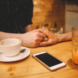 man and woman holding hands in coffee shop