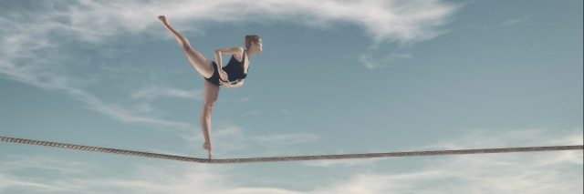 woman walking on a tightrope above a city