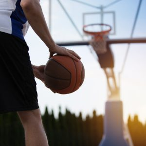 basketball player on court with sun and trees behind net