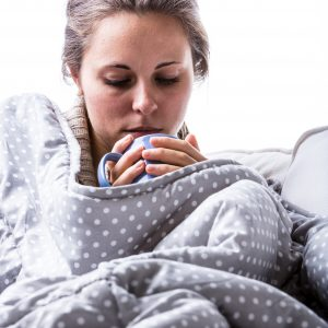 woman wrapped up in blanket on sofa