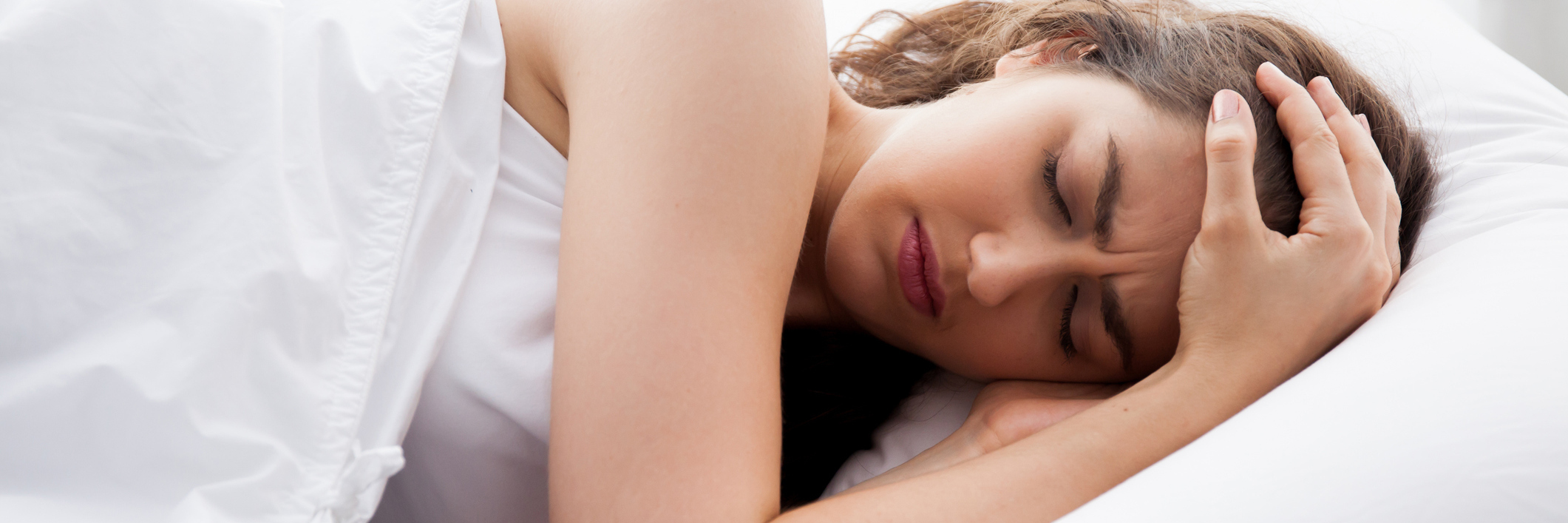 woman lying in bed looking frustrated and in pain