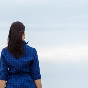Woman facing sky with light clouds