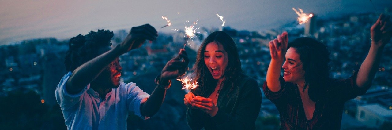 Group of friends celebrating with sparklers at night on rock with scenic view on city