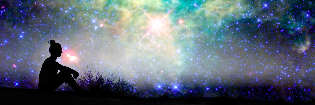 silhouette of woman sitting outside under starry night sky
