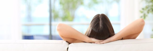 woman relaxing on the couch with her arms behind her head