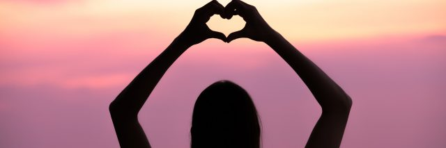 Woman making a hand shaped heart at sunset.