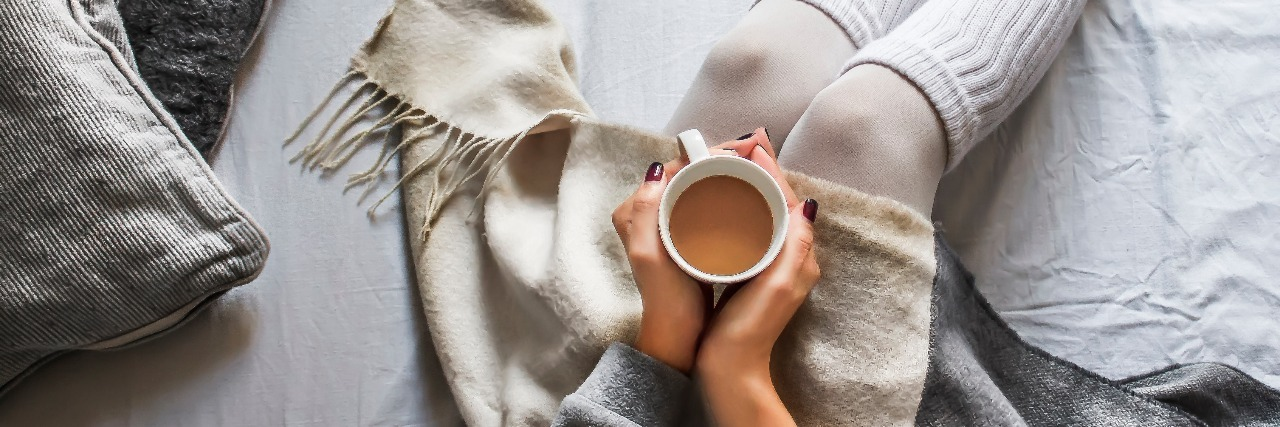 young woman sitting on bed holding a cup of coffee