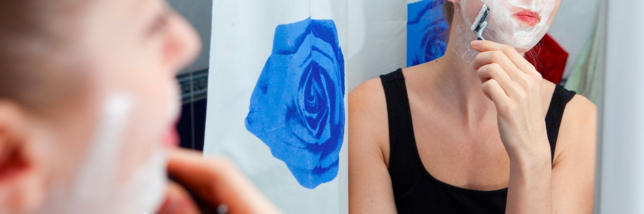 girl shaving face in bathroom mirror