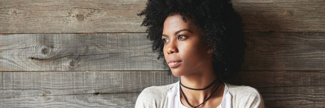 African American woman standing in front of a wooden panel wall, arms crossed.