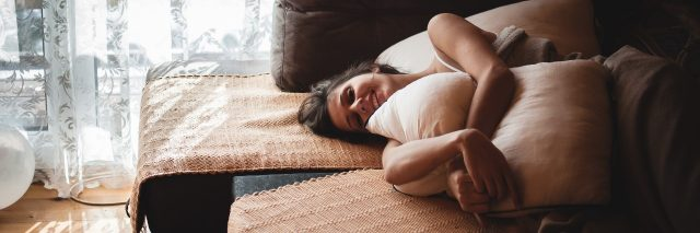 young woman happy in morning sunshine lying in bed