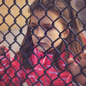 young sad, girl looking through a fence