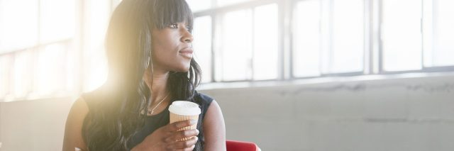 woman sitting in an office chair holding coffee and looking out the window