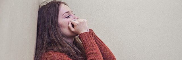 woman leaning against wall in despair and sadness with hands to mouth