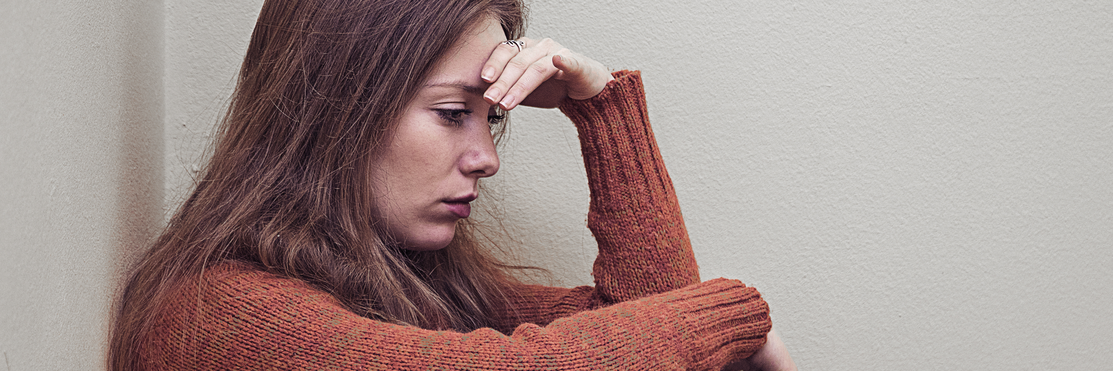 woman sitting alone in corner with depression