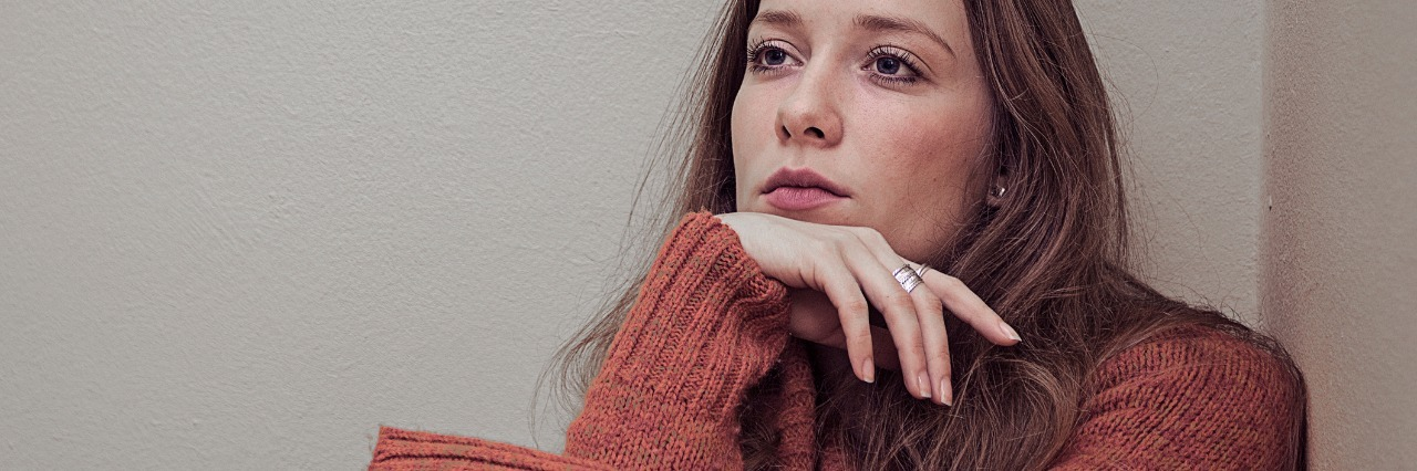 woman looking anxious sitting in corner