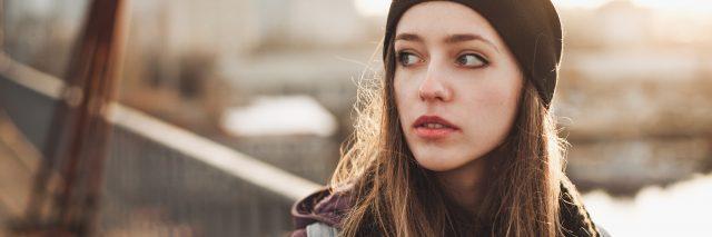 young woman wearing hat walking along bridge