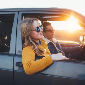 woman leaning out a car window on a road trip with the sun behind her