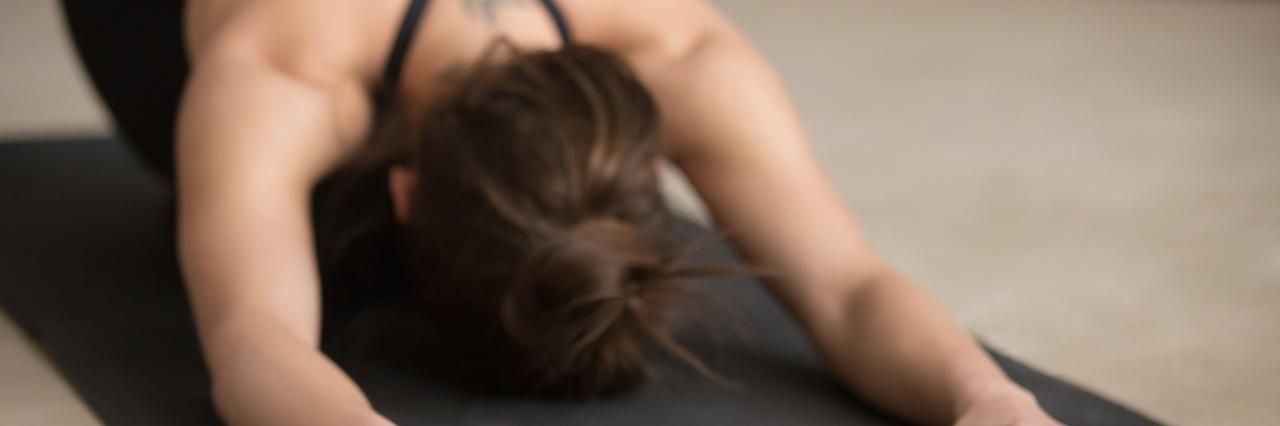 young woman doing yoga, downward dog position