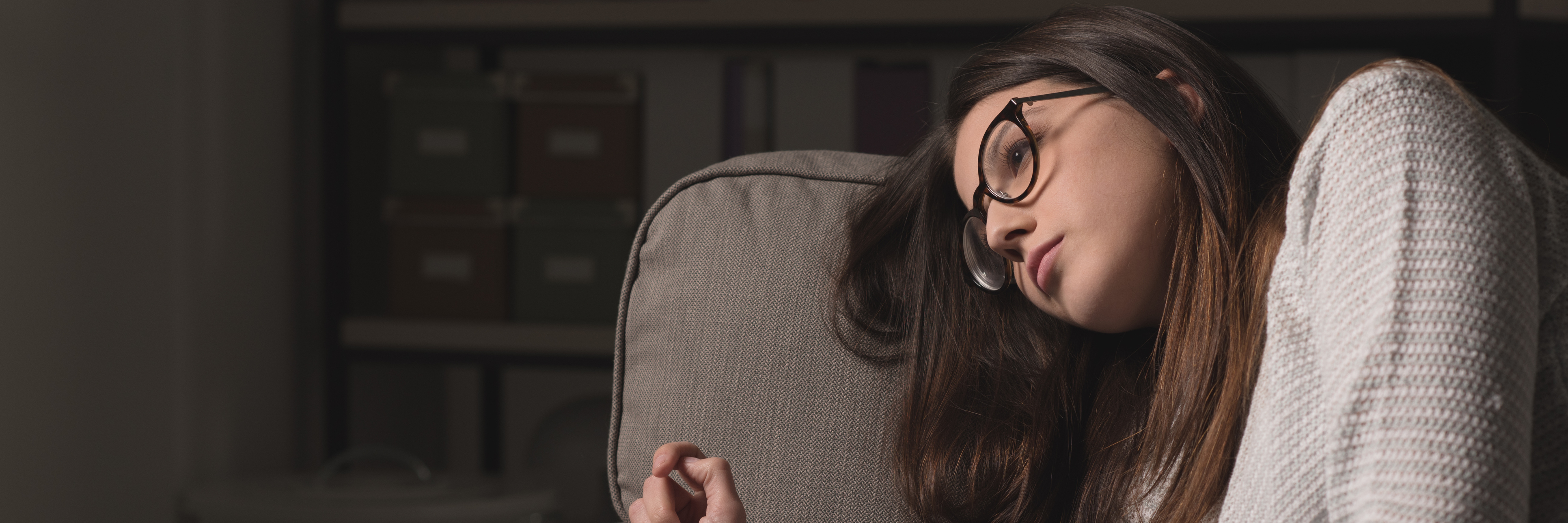 sad young woman with glasses sitting on couch at home exhausted
