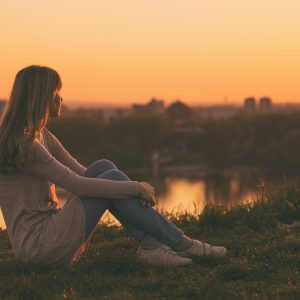woman sitting on a hill overlooking a city during sunset