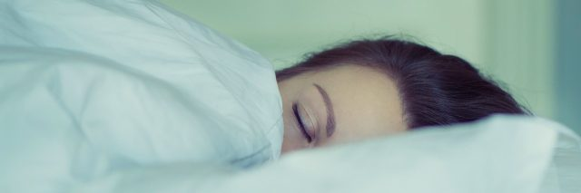 girl in bed with blankets pulled up to eyes