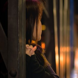 young woman leaning on bridge with blurred background at night