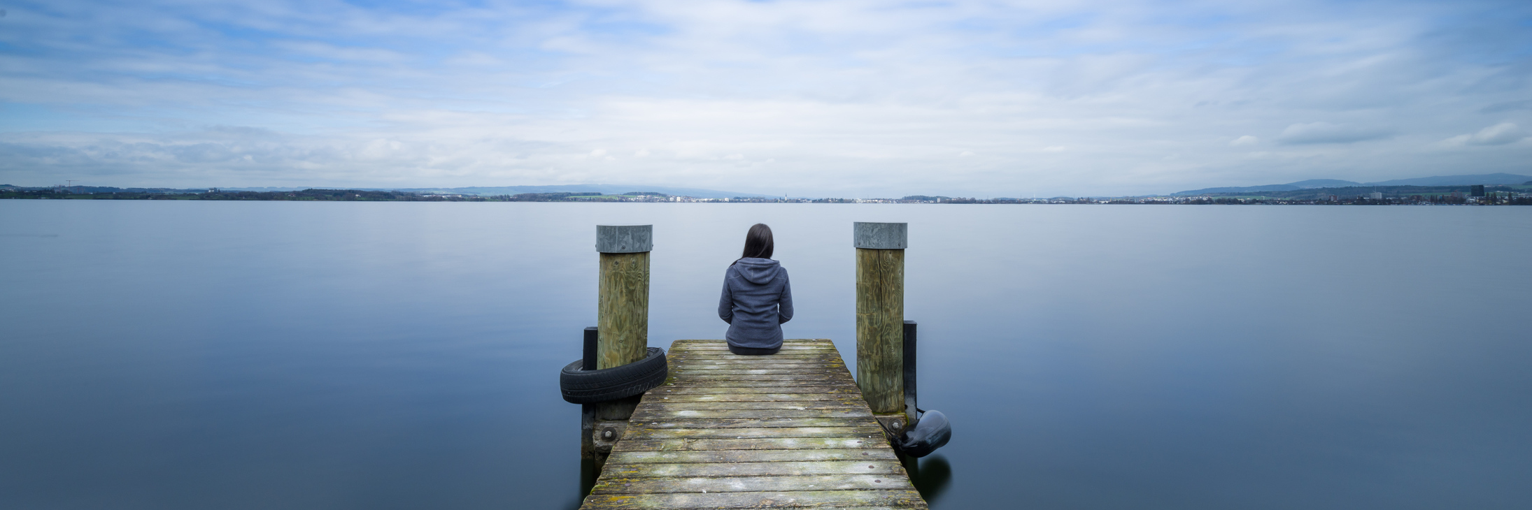 woman sitting on wooden pier on still lake