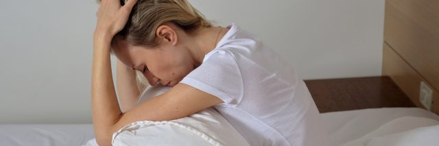 woman sitting in bed frustrated
