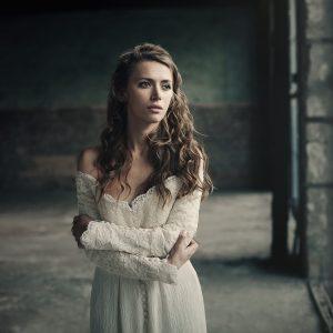 woman in white vintage dress standing by loft window looking upset