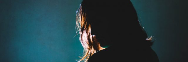 silhouette of woman standing in the dark with light shine behind