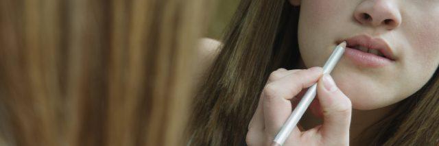 woman applying lip liner in mirror